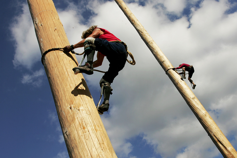 Greg Bisbey, 56, left, and his son Sam, 20, right, race against each other during the Pole Climbing event of the International Lumberjack show on August 28, 2010. Wearing trombone spurs that allow them to grip the wood as they climb, the racers run up the 70-foot high wood poles, the equivalent, Bisbey says, of running about 5 miles.