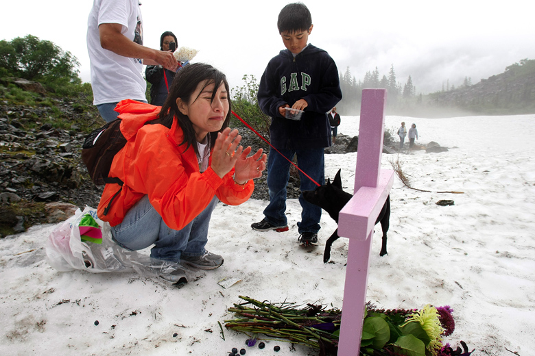 Tamami Tam, center, breaks down after placing blueberries and popcorn - two of her daughter's favorite foods - around the memorial that she set up with her husband John, and son William, 10, right, for her 11-year-old daughter Grace, who died last year when a piece of ice broke off and killed her at the Big 4 Ice Caves in the Mount Baker-Snoqualmie National Forest. The Tams and family friends hiked to the Ice Caves on July 31, 2011 in remembrance of Grace, and erected a cross in her honor at the spot where she died. Sunday was the first time that the Tams had been back since the accident.
