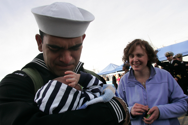 Nisse Fonseca meets his 3-week-old baby Cuper when the USS Abraham Lincoln returned to its homeport in Everett on March 24, 2011 after a 6-month deployment in the Western Pacific and U.S. Central Command areas of responsibility. Fonseca's wife, Sarah, looks on.