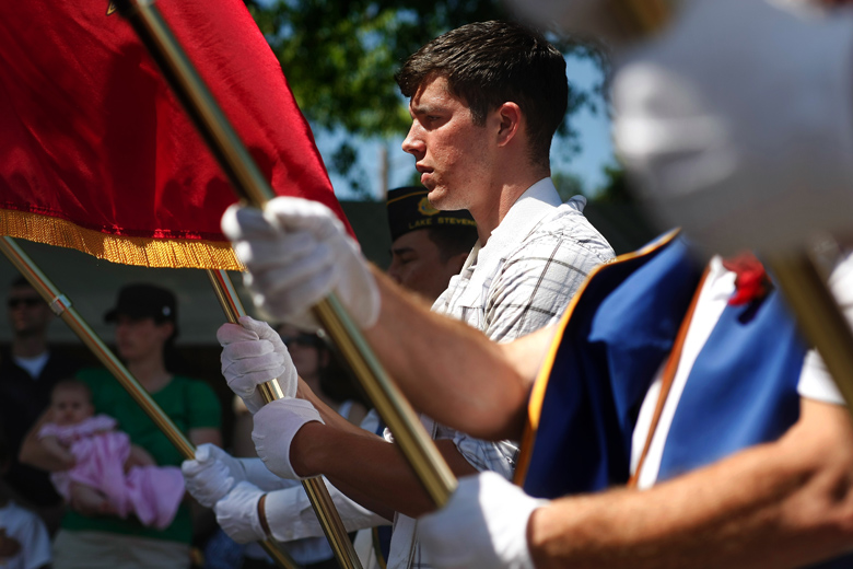 "Jordan, carrying the Marine Corps flag, marches in the Aquafest Parade with other members of the Lake Stevens American Legion. It was the first time that Jordan had been a part of such a celebration as a veteran, and he was proud of that. Going through the motions of marching, though, and of bearing the flag, and listening as taps were played, brought him back to his time of service. ""It's too close to let go of myself and enjoy myself,"" he said when the parade ended."