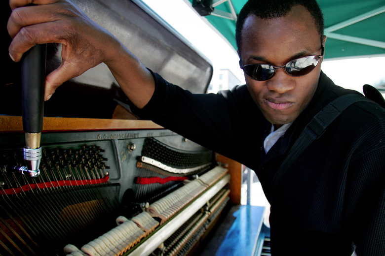 Wilson Charles, a blind piano tuner, works on the Everett Street Tunes piano at the corner of Wetmore and Hewitt on August 11, 2010. Wilson, who is originally from Haiti, started playing the piano when he was 15 years old, and started tuning when he was in his mid-20s.