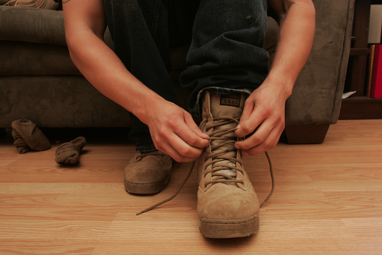 Jordan laces up his combat boots in his bedroom before the Aquafest parade in Lake Stevens. He still regularly wears the boots, which he wore daily in Iraq and Afghanistan. The rest of his belongings from his time of service, though, remain unpacked in his Seabag in the garage.