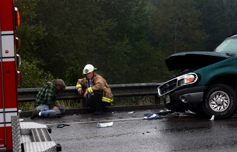 Lawrence Ottow, left, mourns the death of his son, Rocky Ottow, at the site of the crash that occurred on September 17, 2011 on U.S. 2, east of Highway 9. Rocky Ottow was the driver of the green Ford Explorer at right, and Lawrence Ottow, who had been driving directly in front of the Explorer when the accident happened, saw it out of his rearview mirror. Three cars were involved in the crash, and six other people were injured.