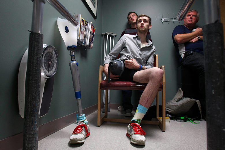 David Ricci, center, with brother, Tyler Perron, 13, and stepfather, Scott Perron, listens to Dr. Dave Hughes during his appointment at Cornerstone Prosthetics & Orthotics in Everett on October 21. David's leg was amputated after he was hit by a train in India last June. During the appointment, David was fitted with a temporary prosthetic, and took his first steps.