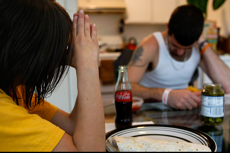 """Kaeden Torrance says a short, improvised prayer as Aaron bows his head before dinner on June 6 at their Everett apartment. """"I used to despise him and hate him,"""" Torrance says about God. """"But not anymore."""""""