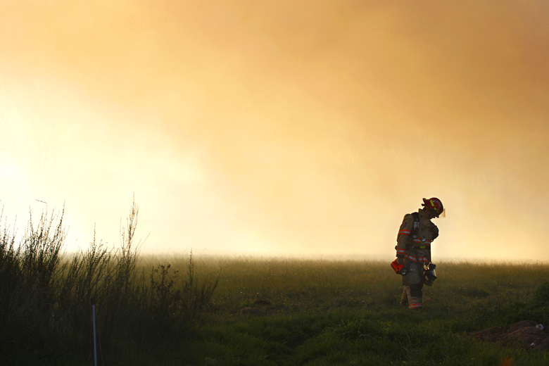 An Arlington firefighter walks through the smoke during a fire at the National Food Corporation egg processing plant in Arlington on November 10, 2010. The fire caused an estimated $1.5 million in damage.
