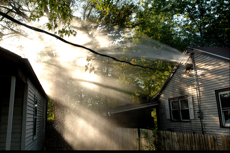 Firefighters worked to put down a small fire that spread from the kitchen to the attic of a home at 1705 N. Valley Avenue in Peoria on Saturday, September 29, 2012. Here, water from a firefighter's hose sprays out of the attic window, at right, after the fire was put out.