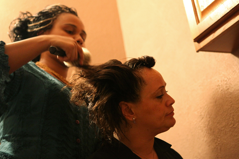 Shawniece Sephus, 18, helps Harris with her hair at their South Peoria home on an evening in December. Sephus, who was taken away from Harris by DCFS when she was born because Harris had cocaine in her system at the time of the birth, spent much of her childhood with a foster family. Two years ago, Sephus came back to live with Harris full-time.