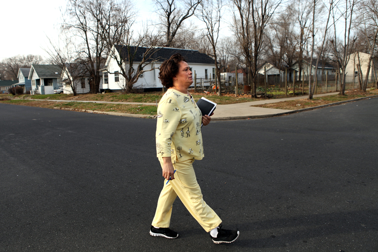 """Cassie Harris walks through her South Peoria neighborhood on Thursday, November 29. She spends some afternoons going door to door, talking to people and trying to gain support for Neighborhood Watch. Harris strongly believes that if the neighborhood takes a united stand against the gang and drug-related violence, the impact will be great. """"We're a gang within ourselves,"""" she told one neighbor. """"As neighbors, we can be strong, and strong together."""""""