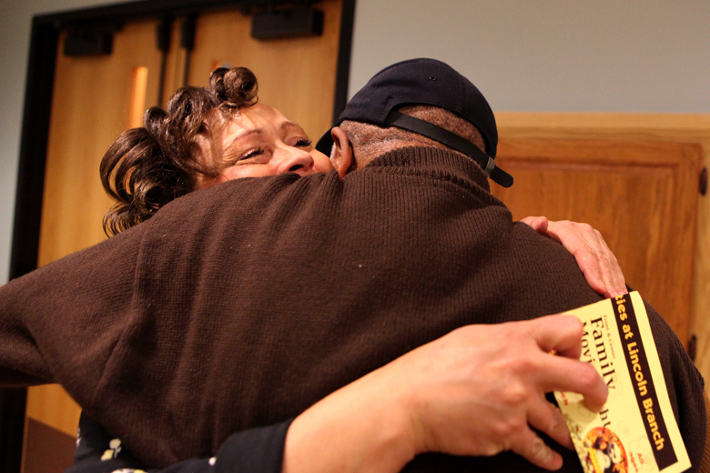 Cassie Harris gets a hug from Gilbert Comer of Peoria after her Red Zone Neighborhood Watch meeting at the Lincoln branch of the Peoria Public Library on Tuesday, December 4. Harris organized the meeting as an outreach effort to connect with the community and get support for  Neighborhood Watch.