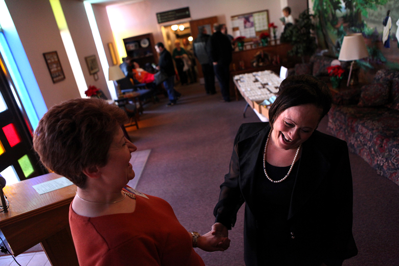 Cassie Harris and friend Laura Baize greet each other before Sunday morning's church service on December 23 at Christ Lutheran in South Peoria.