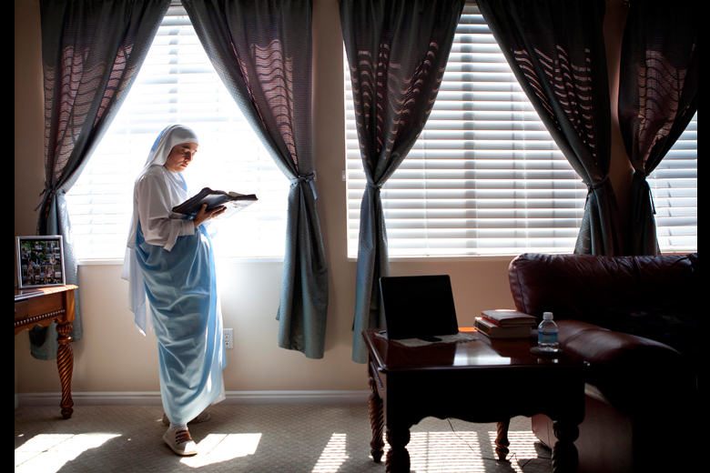 Sister Natasha del sol Eucaristico Caycedo reads her bible as she waits for a pot of water to boil while cooking lunch on Tuesday, April 23, 2013 at the home in Lindon where she and Sister Teresa de Jesus Ventura are staying while they're in Utah. The Sisters are 35-year-old Catholic Nuns from Columbia, here for a couple months studying English and working with local Catholics. Back in Columbia, they're part of the Eucharistic Communicators from Heavenly Fathers, a community of 64 nuns who live on a farm, and who, in addition to daily prayer, farm their own food and produce spiritual TV programs.   SARAH WEISER/Daily Herald
